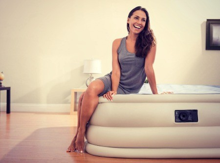 Woman smiling and sitting on air-bed.